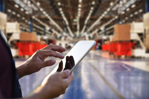 Factory worker using digital tablet to operate automation