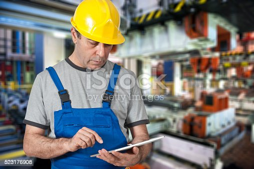 667596352istockphoto Factory worker using digital tablet to operate machinery 523176908