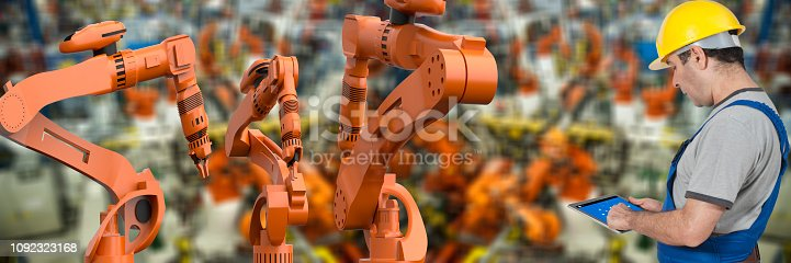 1178819379 istock photo Factory worker using digital tablet to operate Robotic Arm 1092323168