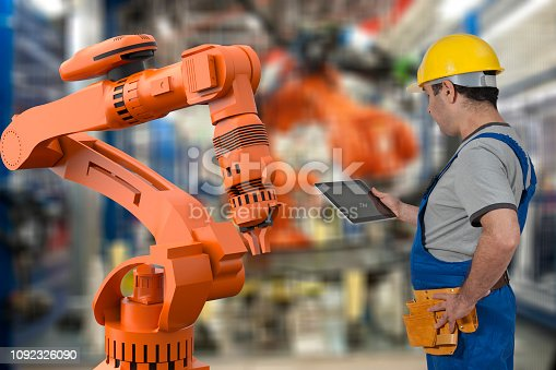 1178819379 istock photo Factory worker using digital tablet to operate Robotic Arm 1092326090