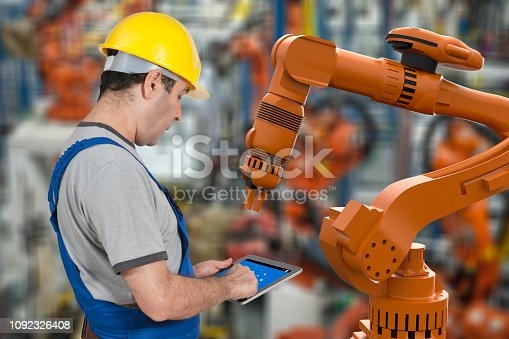 1178819379 istock photo Factory worker using digital tablet to operate Robotic Arm 1092326408