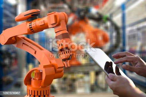 1178819379 istock photo Factory worker using digital tablet to operate Robotic Arm 1092326962