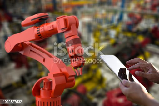 1178819379 istock photo Factory worker using digital tablet to operate Robotic Arm 1092327532