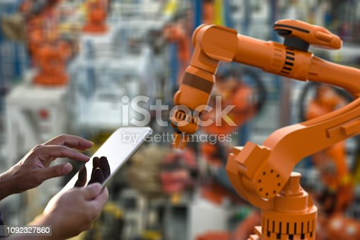 1178819379 istock photo Factory worker using digital tablet to operate Robotic Arm 1092327860
