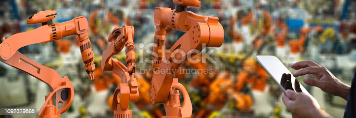 1178819379 istock photo Factory worker using digital tablet to operate Robotic Arm 1092329868