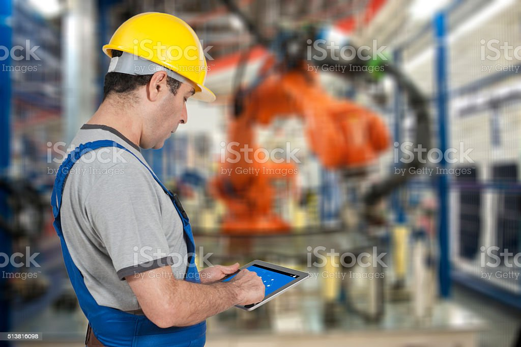 Factory worker using digital tablet to operate Robotic Arm stock photo