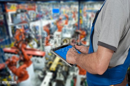 667596352istockphoto Factory worker using digital tablet to operate Robotic Arm 678130448