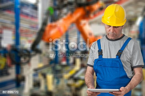 667596352istockphoto Factory worker using digital tablet to operate Robotic Arm 851899770