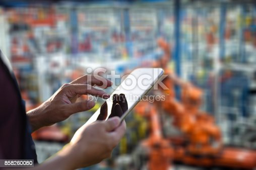 667596352istockphoto Factory worker using digital tablet to operate Robotic Arms 858260080