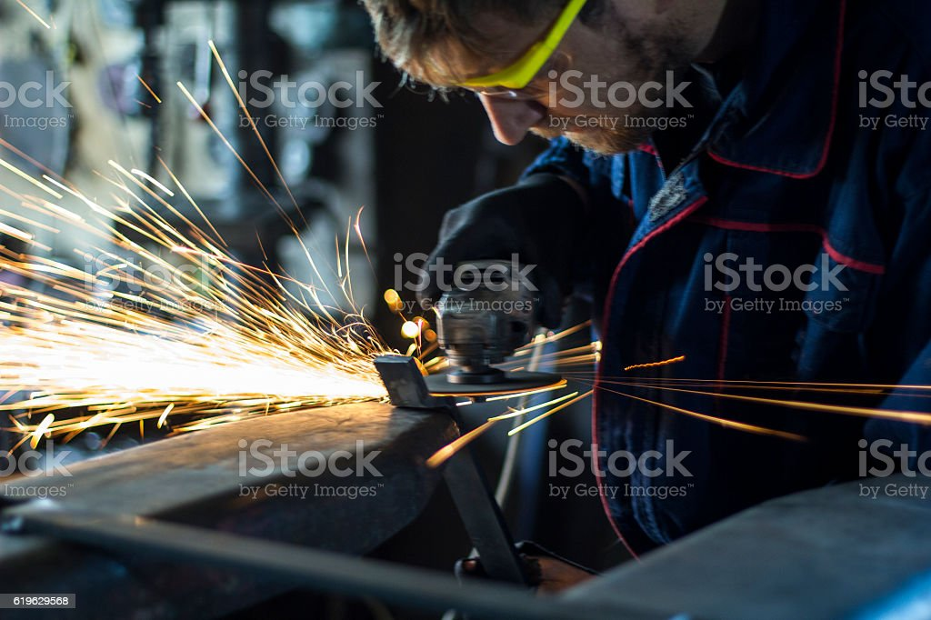Factory worker using electric grinder in METAL INDUSTRY. stock photo