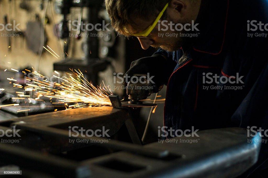 Factory worker using electric grinder in METAL INDUSTRY. foto royalty-free