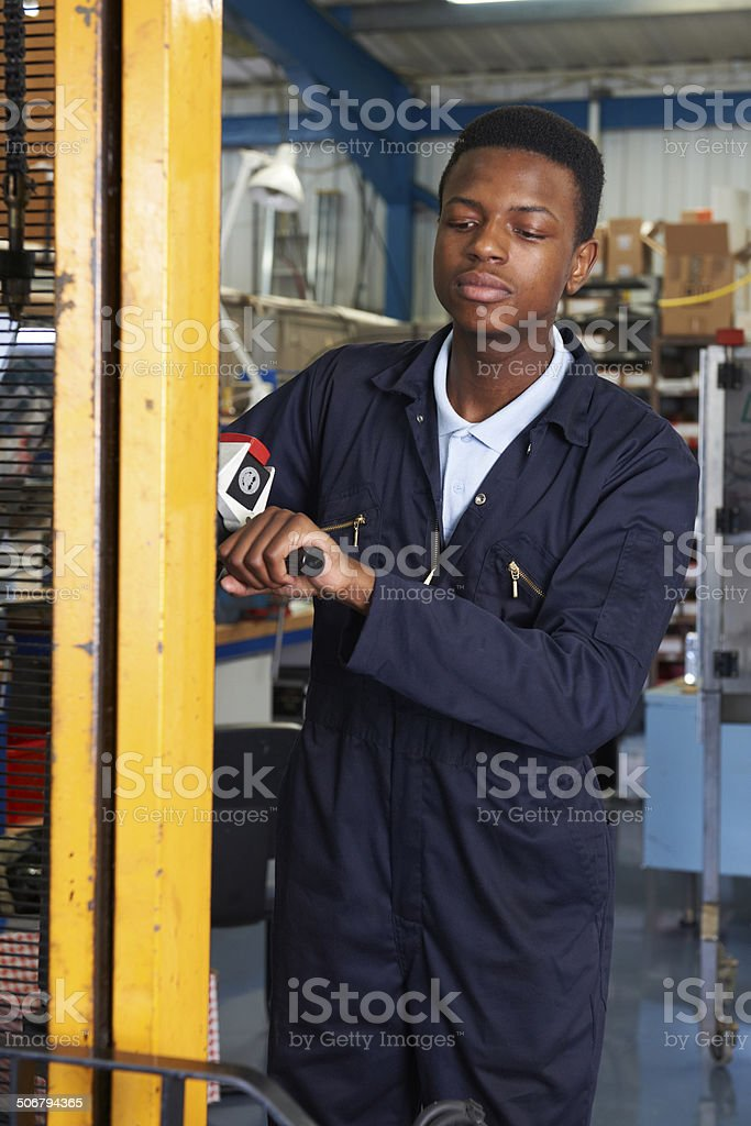 Factory Worker Using Powered Fork Lift To Load Goods stock photo