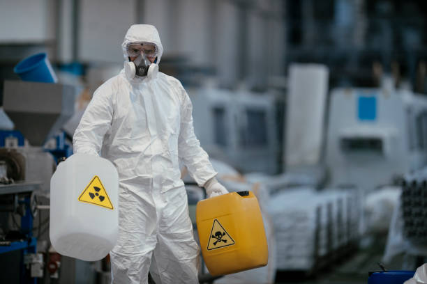 Factory worker wearing gas mask and radioactive protection suit stock photo