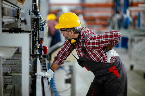 Factory worker with painful back injury stock photo stock photo
