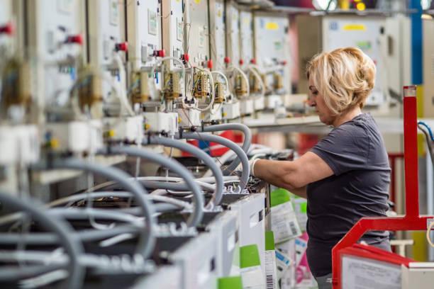Operário de fábrica, trabalhando na linha de produção - foto de acervo