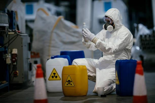 factory worker working with dangerous materials - tuta protettiva foto e immagini stock
