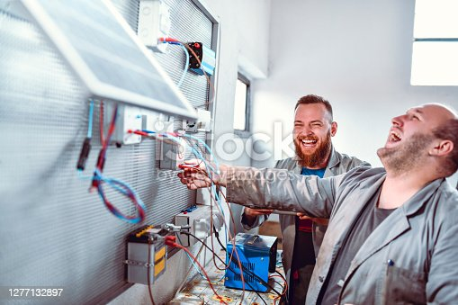 Factory Workers Laughing At Jokes While Working Together