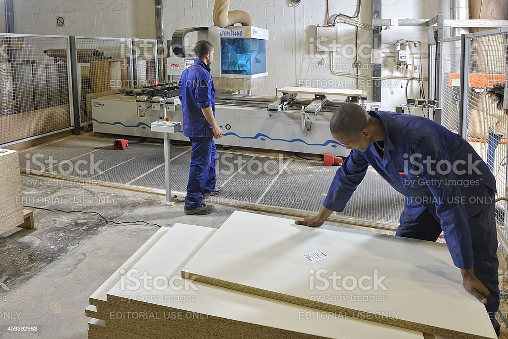 Factory workers load wooden sheets stock photo