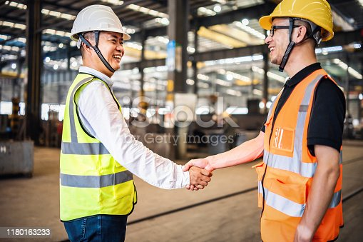 Factory workers shaking hands.