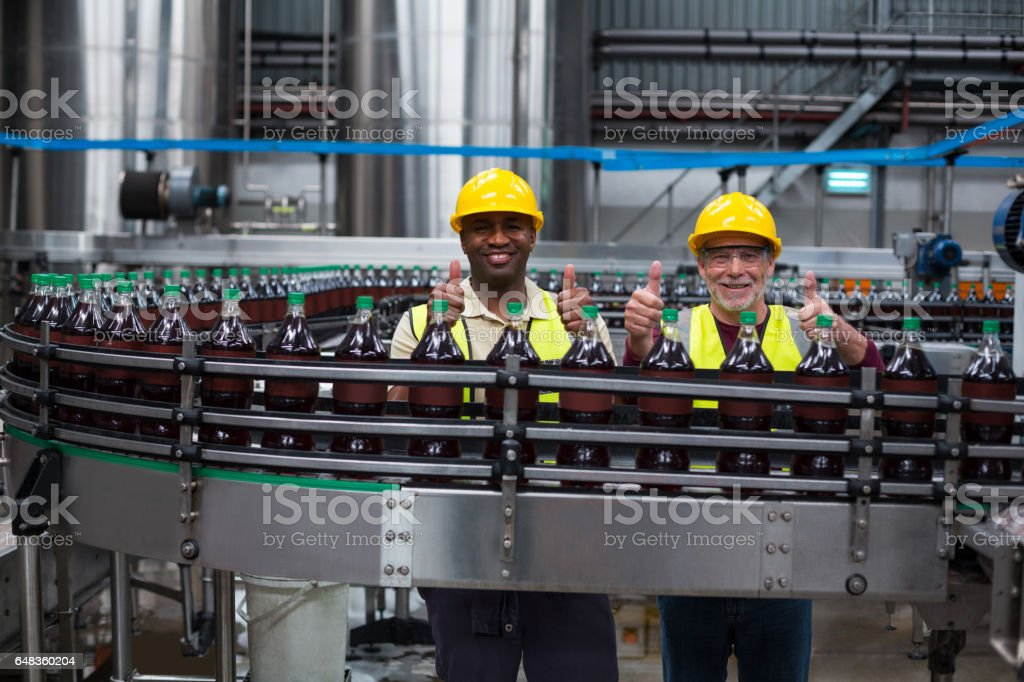 Factory workers showing their thumbs up at drinks production line stock photo