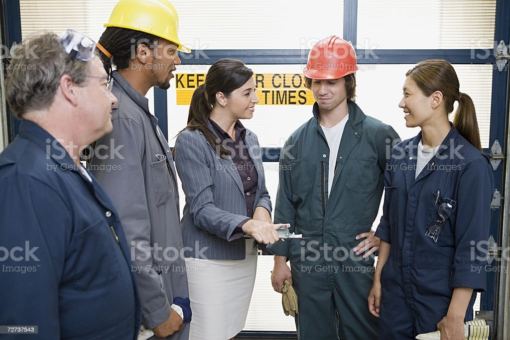 Factory workers talking to manager stock photo