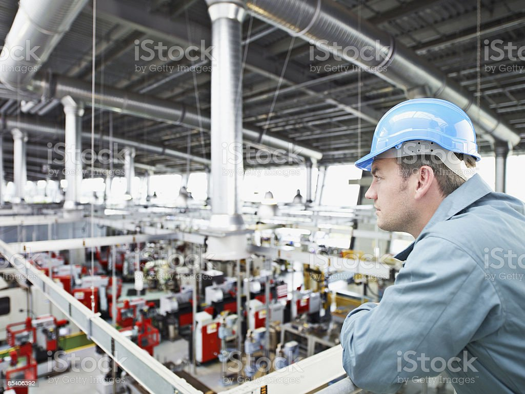 Factory-worker in hard-hat looking at factory floor stock photo