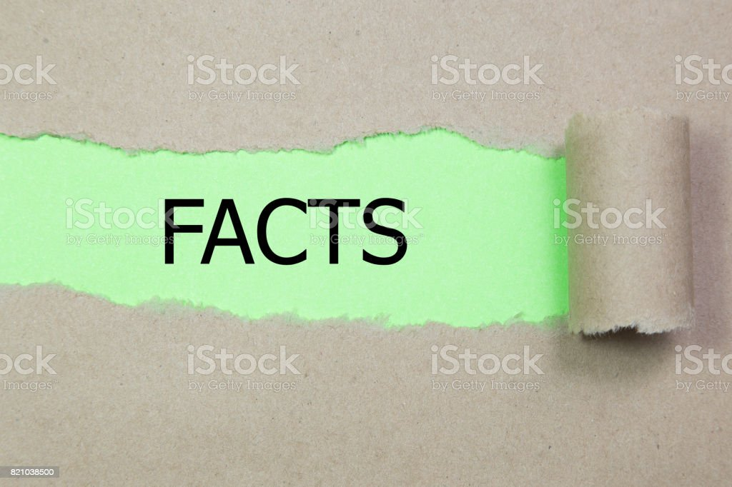 facts message written under torn paper stock photo