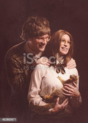An awkward loving young couple with 1970's - 1980's vintage style poses for a portrait, holding a stuffed squirrel like its a baby.  Retro-styled; INTENTIONAL DEGRADATION OF IMAGE AND LIGHTING.