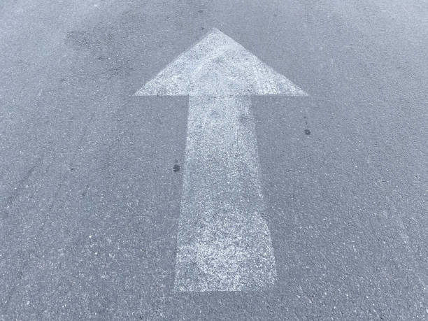 faded white direction directional in or out arrow on asphalt entrance drive or road stock photo