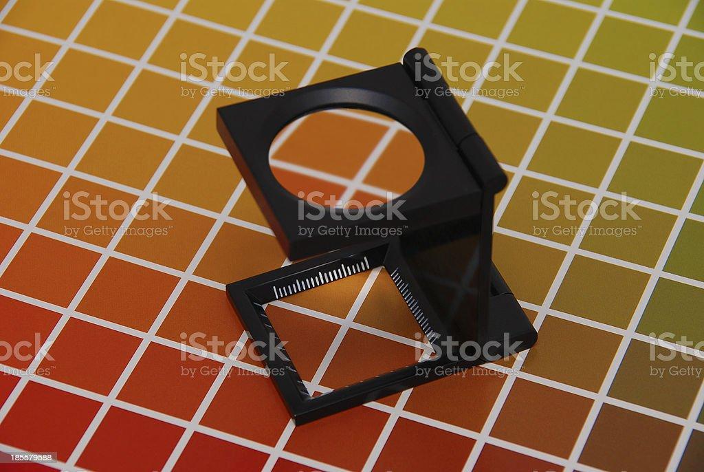 Fadenzähler auf Farbkarte / Linen tester on color chart stock photo