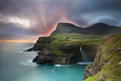 High angle longexposure shot of the small village Gásadalur and the Mulafossur waterfall in the foreground at sunset on Faroe Islands.