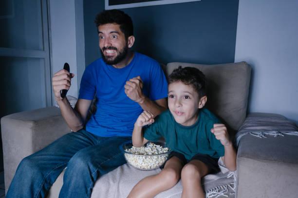 Fahter e filho assistindo TV e torcendo à noite - foto de acervo