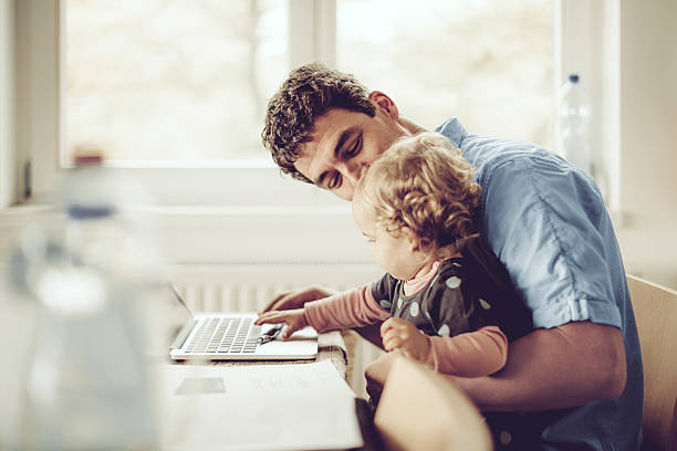 Fahter is showing his daughter things on a laptop stock photo