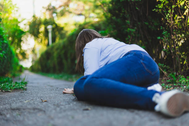 Fainting woman lying down while having heart pain outdoors stock photo