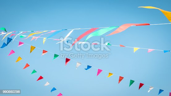 istock Fair flag blur bunting background hanging on blue sky for fun festa party event, summer holiday farm feast celebration, carnival festival event, park or street design decoration element 990660298
