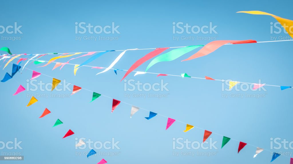 Fair flag blur bunting background hanging on blue sky for fun festa party event, summer holiday farm feast celebration, carnival festival event, park or street design decoration element stock photo