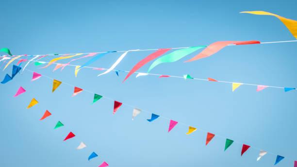 eerlijke vlag vervagen bunting achtergrond opknoping op blauwe hemel voor leuke festa partij event, zomer vakantie boerderij feest feest, carnaval festival evenement, park of straat decoratie ontwerpelement - traditioneel festival stockfoto's en -beelden