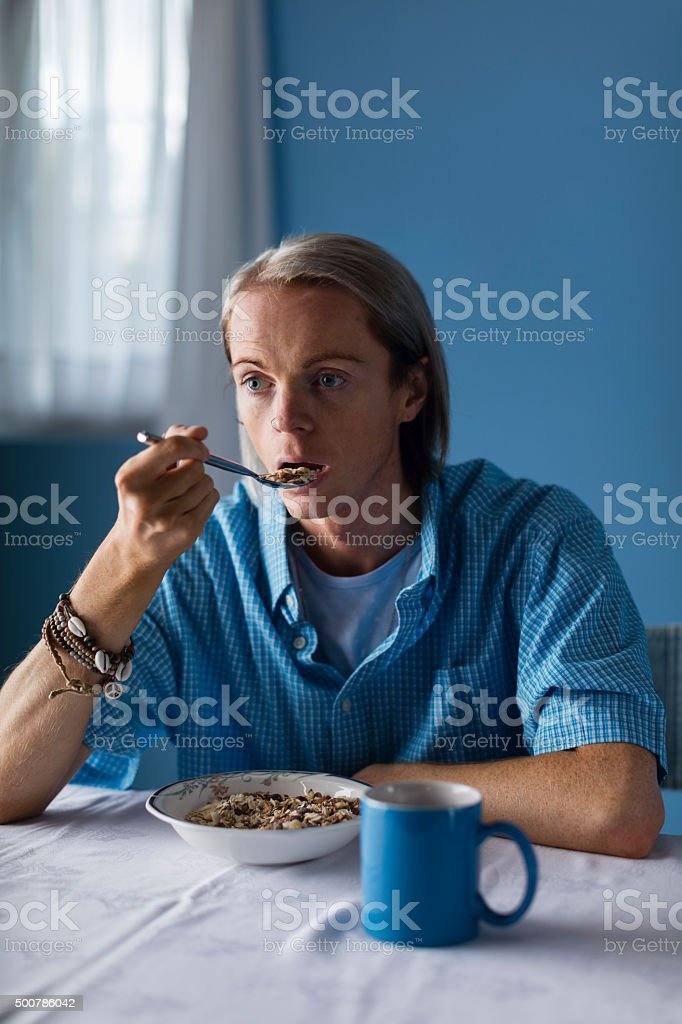 Blue and white shot of a fair-haired man in his 30s eating cereals...