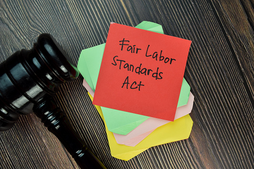 Fair Labor Standards Act write on sticky note isolated on Wooden Table. Justice/Law concept