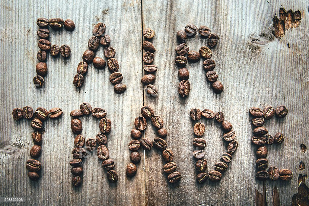 An overhead view of fresh, aromatic roasted coffee beans spelling out...