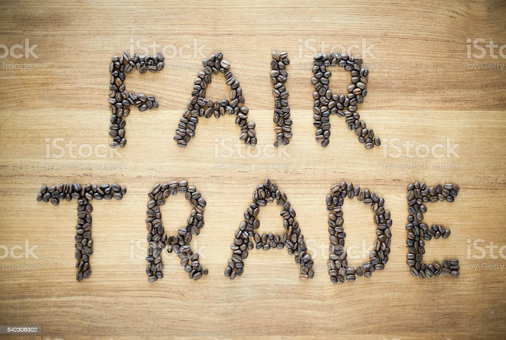 fair trade sign by roasted coffee beans stock photo