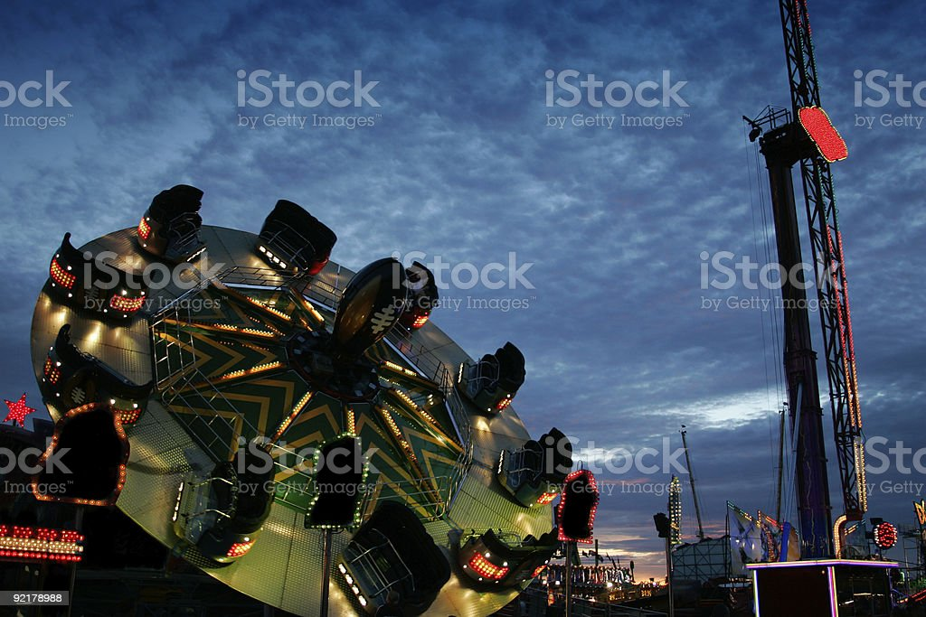 Fairground at dusk Fairground at dusk. Amusement Park Stock Photo