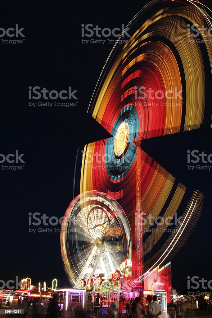 Fairground at night. Fairground at night, great spinning motion trails from the lights. Amusement Park Stock Photo