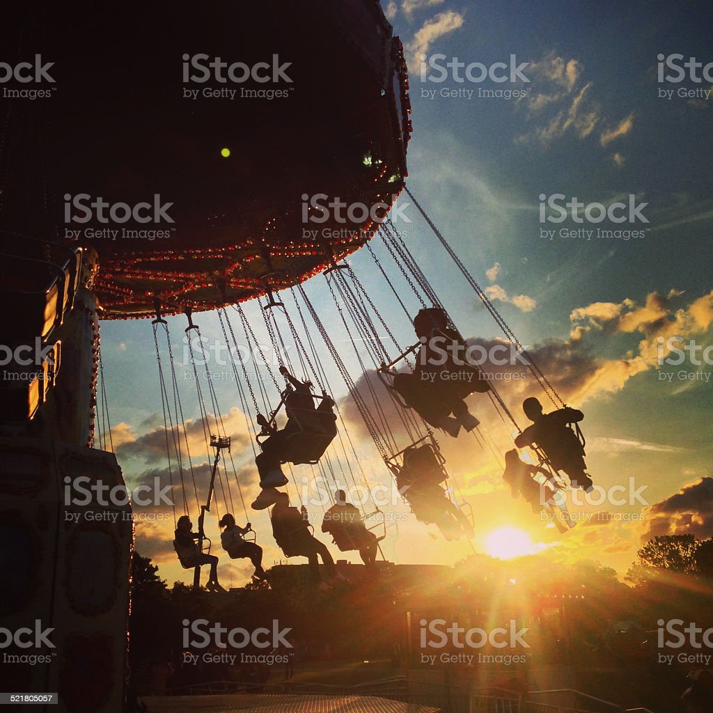 fairground ride at sunset stock photo