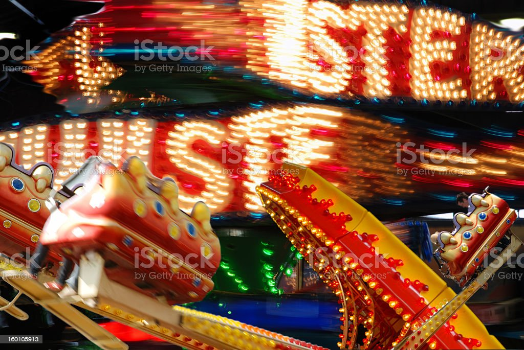 A fairground ride lit up brightly at night stock photo