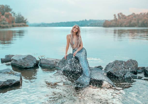 blonden meerjungfrau in liebe träumt von schönen prinzen, neue geschichte ariel, image von märchen sirene mit langen schwanzflosse, schicke krone von muscheln, theaterstücke, streusel klares wasser, ökologie der umwelt - abendkleid lang blau stock-fotos und bilder