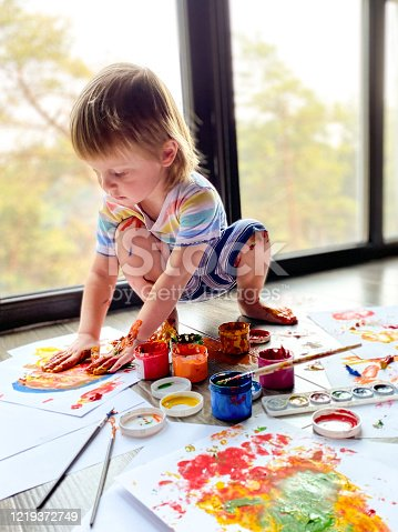 A fair-skinned little child / infant, draws with colorful paints against the background of a large panoramic window at home.