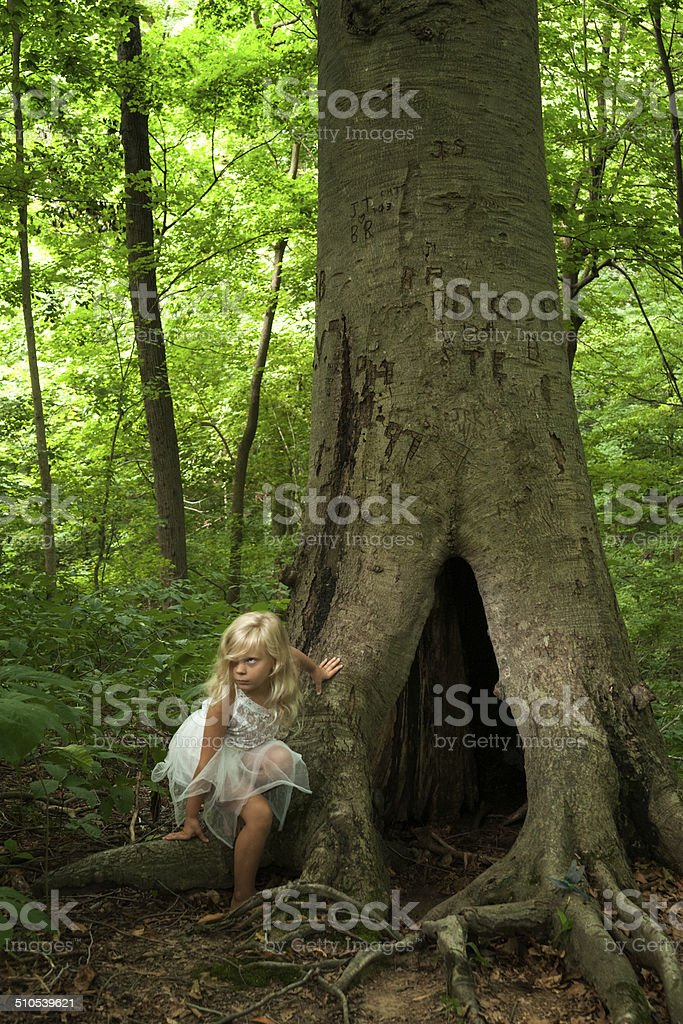 Fairy child crouches against tree in forest stock photo