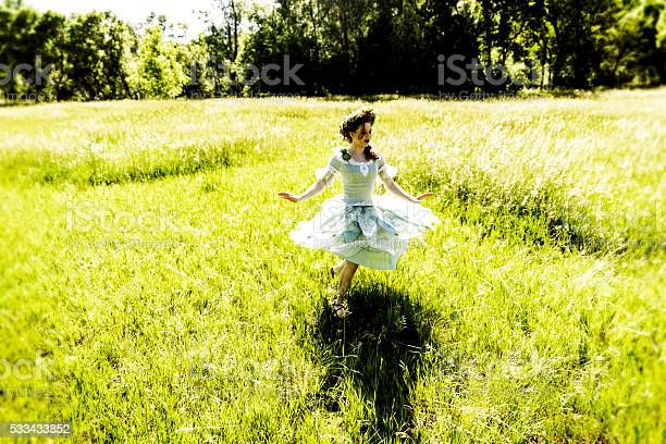 A young women in fairy outfit dancing in a grassy field.