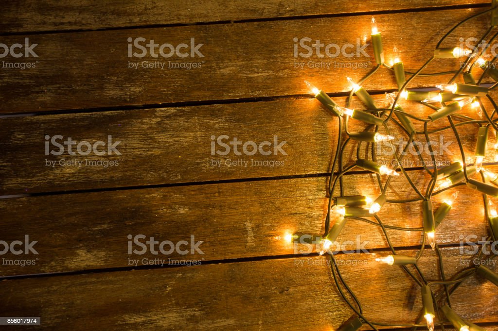 Fairy lights laying on a wood table ready to be used. stock photo
